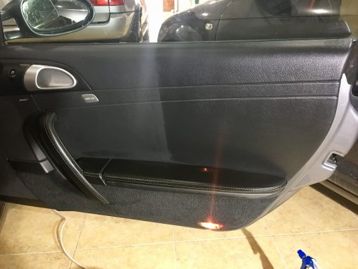 Antes y después del proceso de limpieza y acondicionado de la puerta de un Porsche 911 Carrera